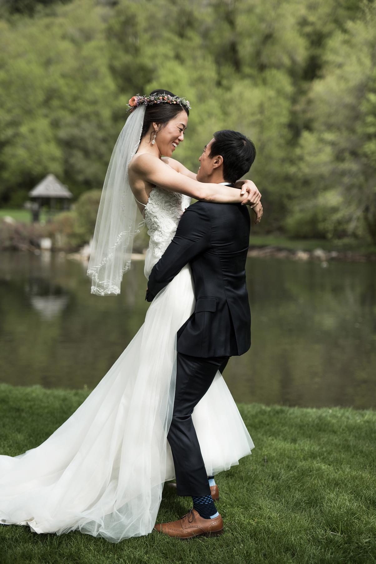 groom sweeping up his bride in the utah mountains