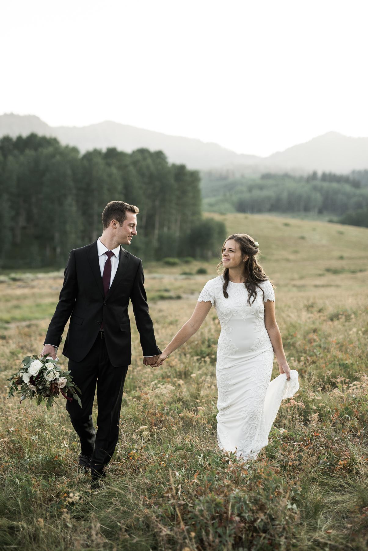 couple walking through open field