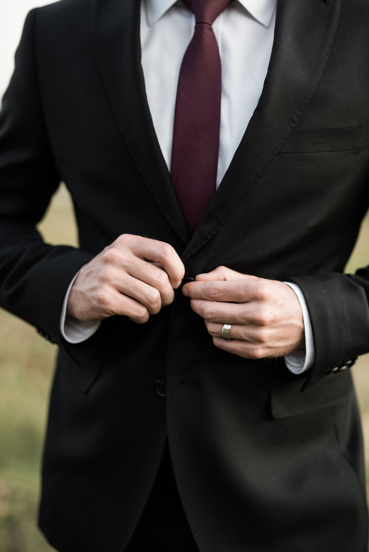 groom buttoning up jacket