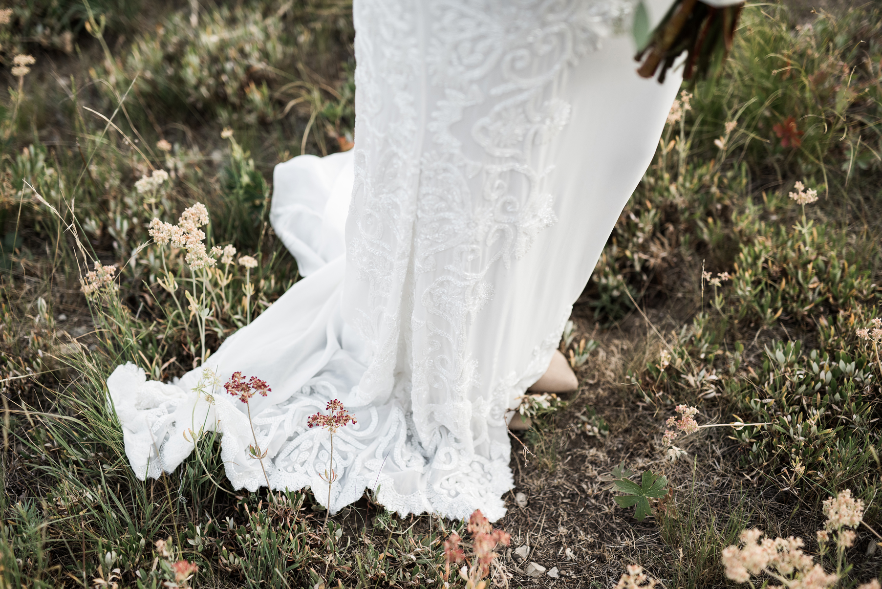 intricately beaded wedding gown in mountains