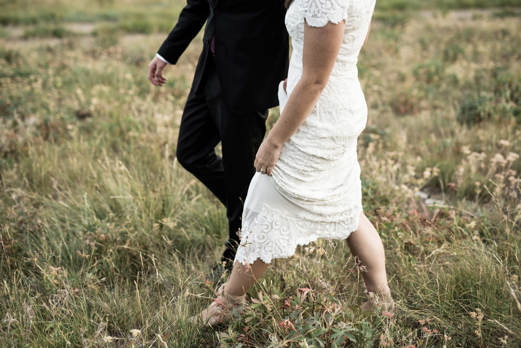 bride and groom walking through mountain field