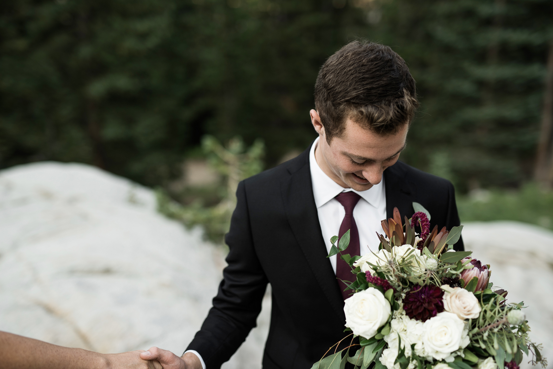 groom helping bride off of a rock