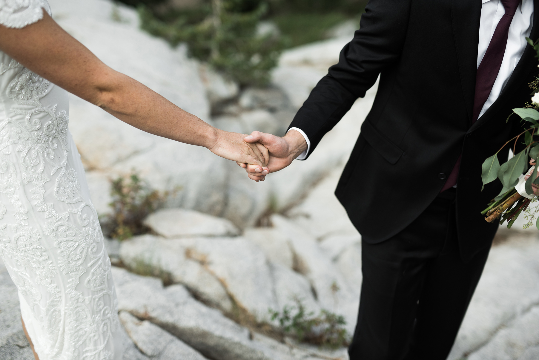 couple holding hands on a large rock