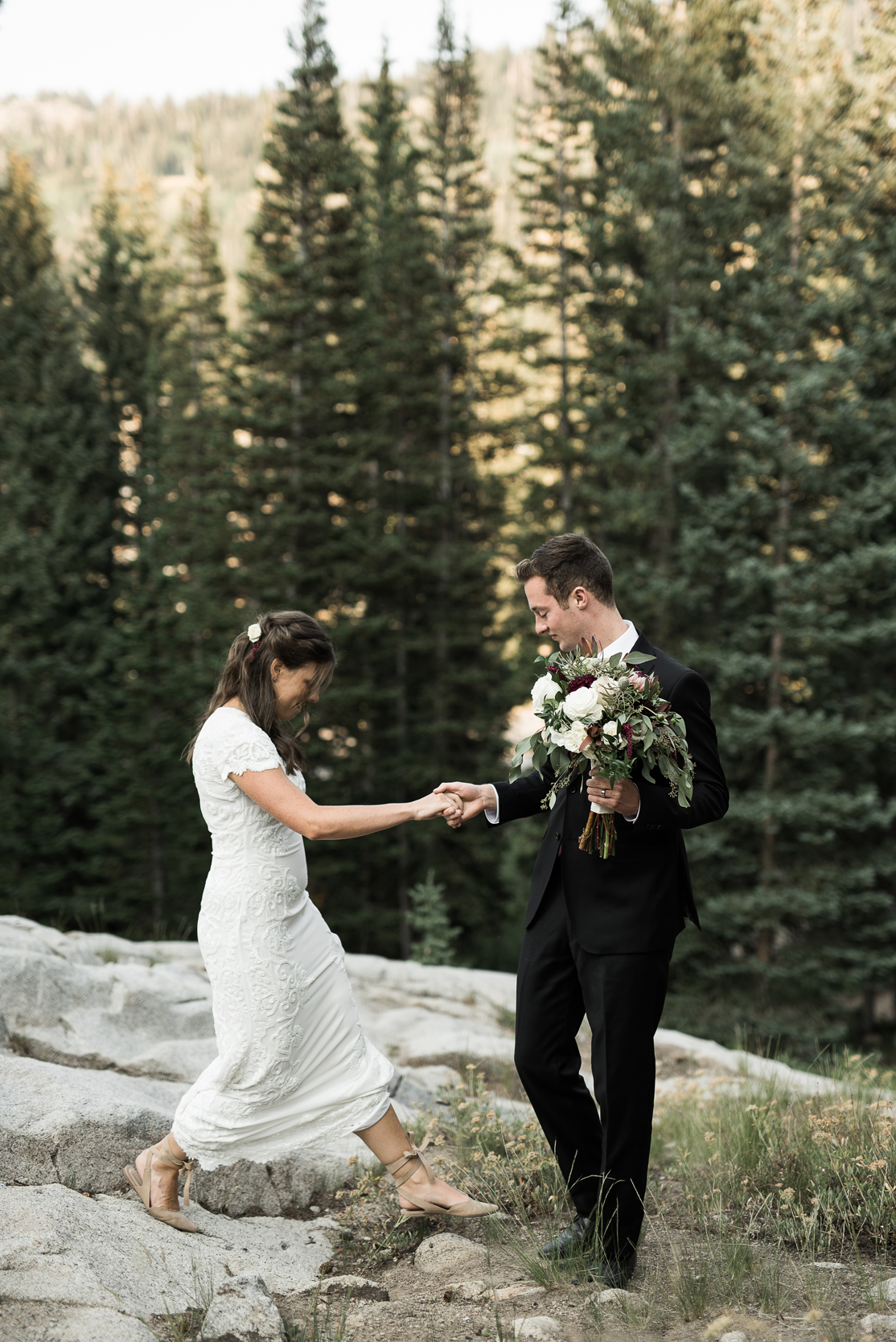 bride and groom helping each other down a boulder