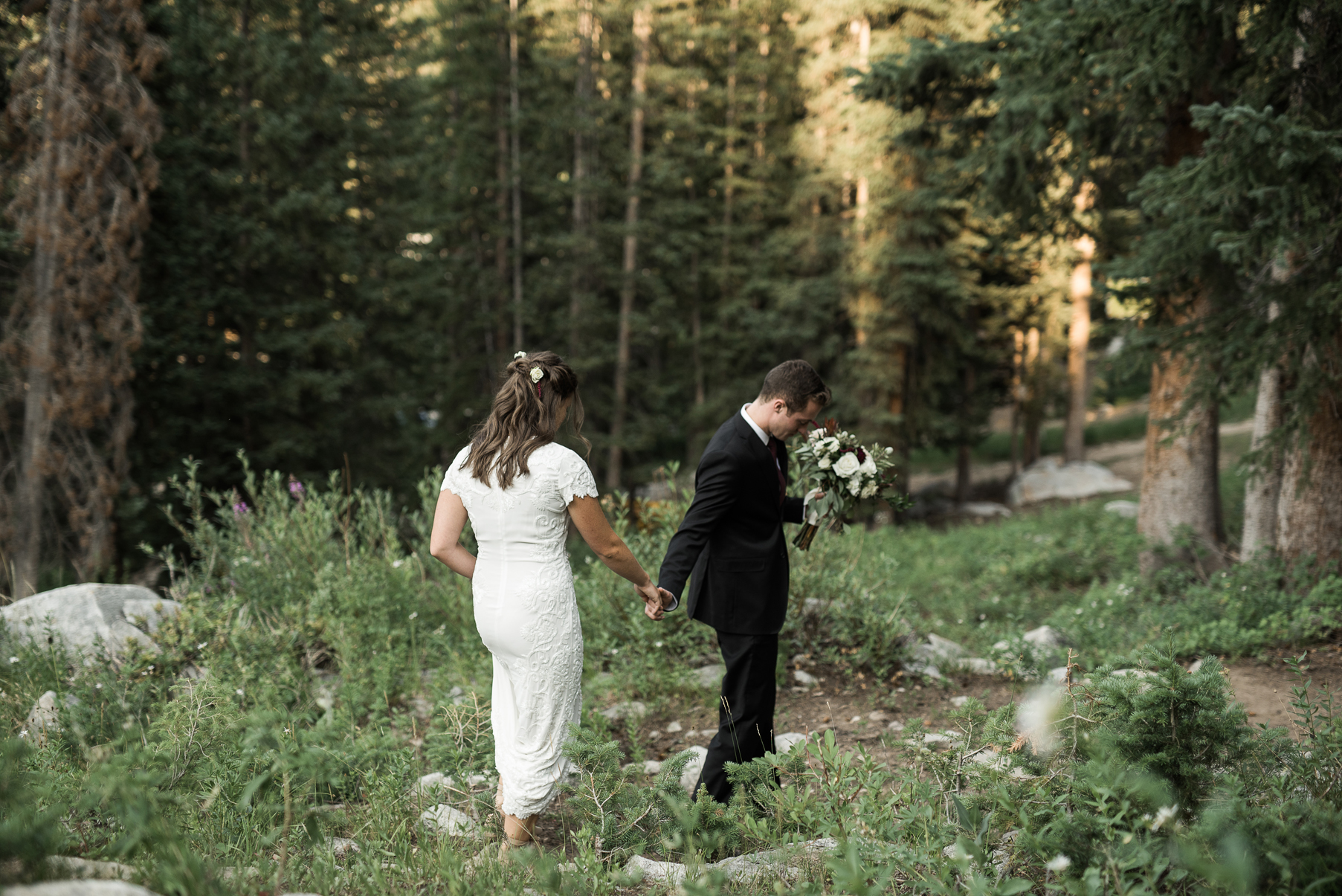 bride and groom walking together through mountains