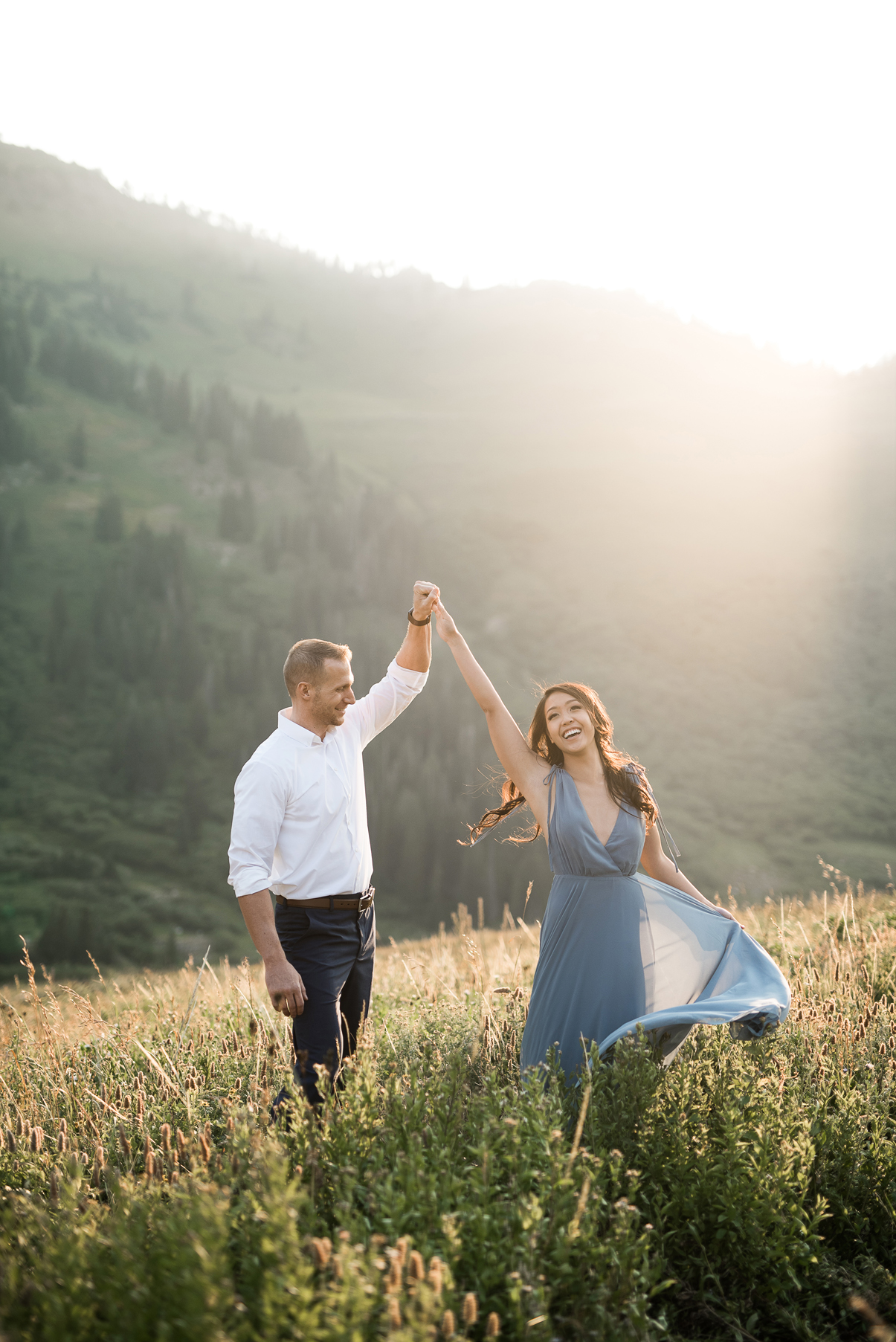 groom spinning his bride in the mountains