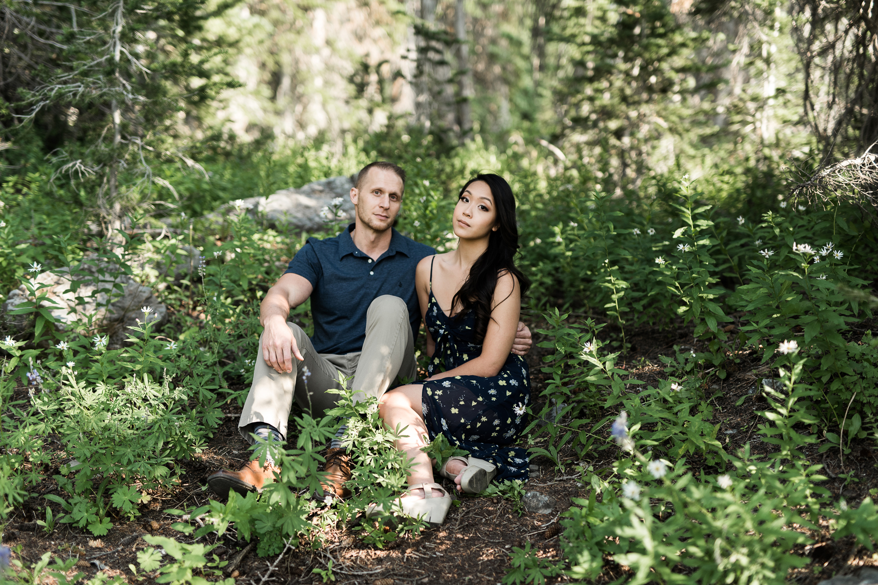 Couple sitting in lush green grass and wildflowers