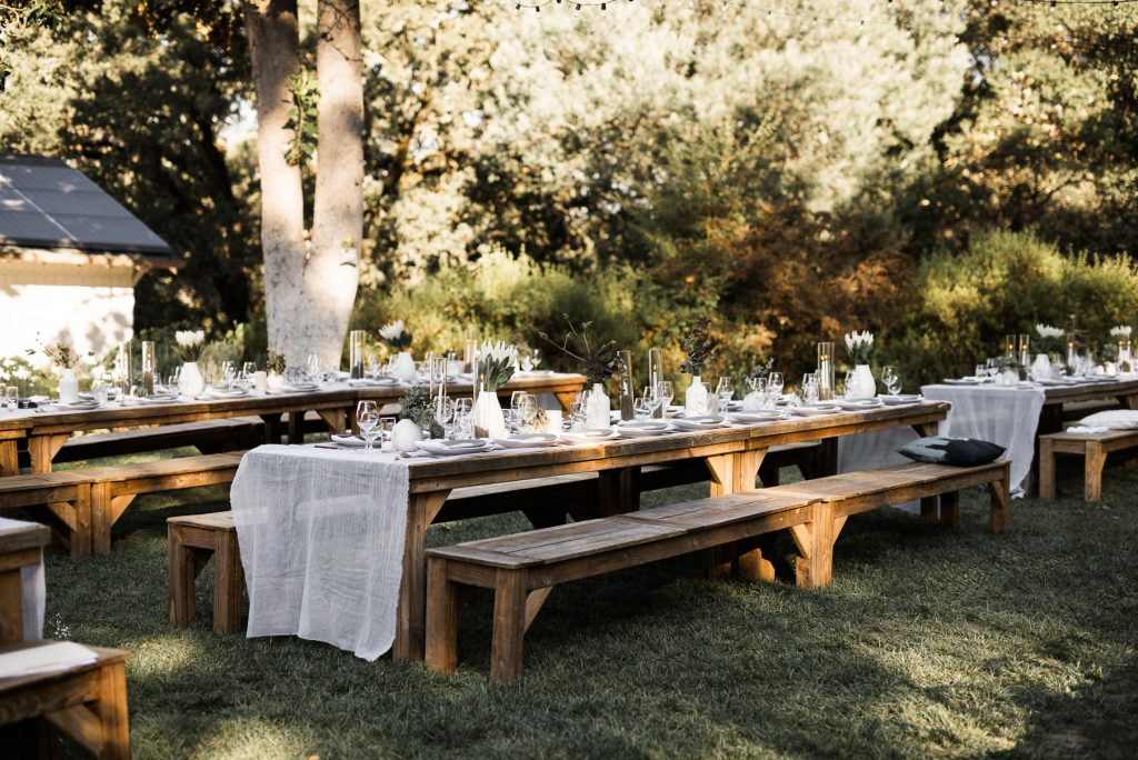 picnic style wedding dinner with long wooden tables
