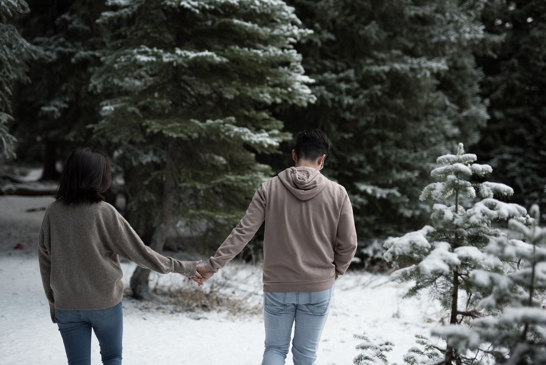 couple walking through the snowy mountains