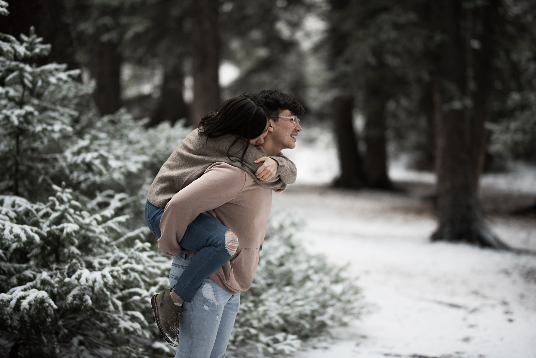 piggyback ride through a snowy grove of trees