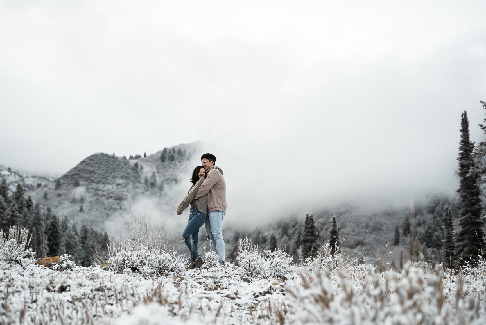 cuddly couple in front of a foggy snowy mountain
