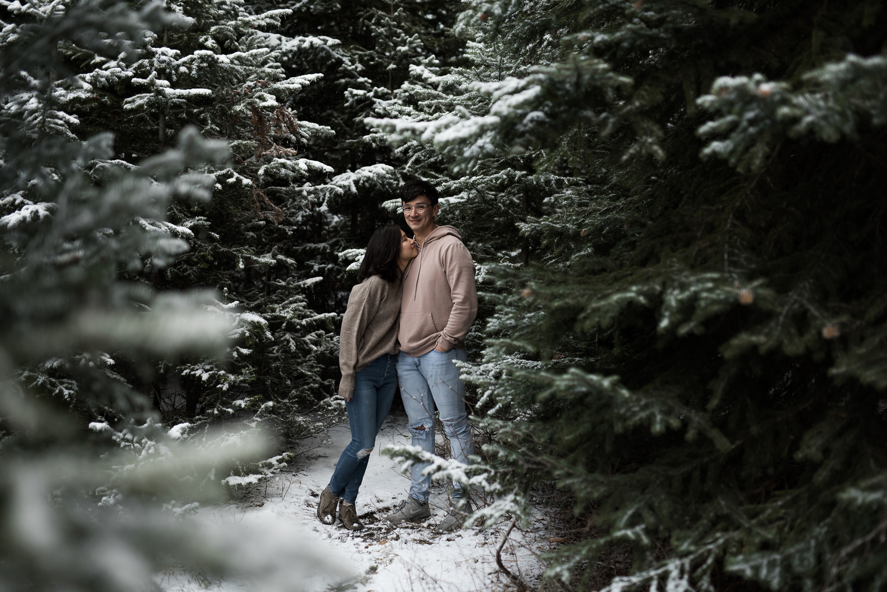 couple cuddling together in thick snowy pine trees