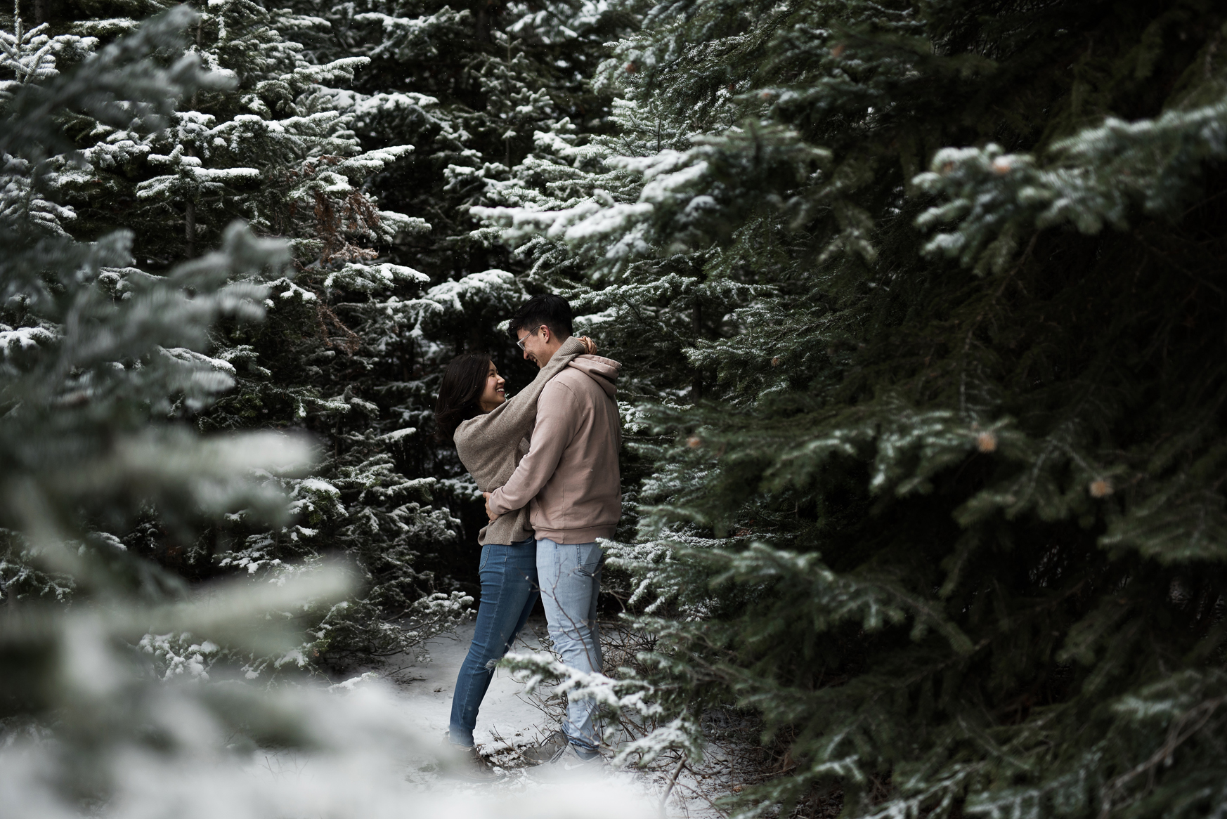 couple cozied up together in snowy mountains