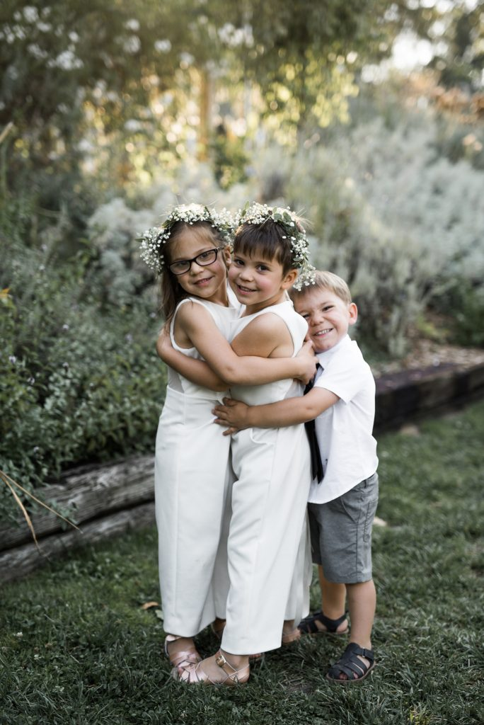 flower girls wearing white jumpsuits