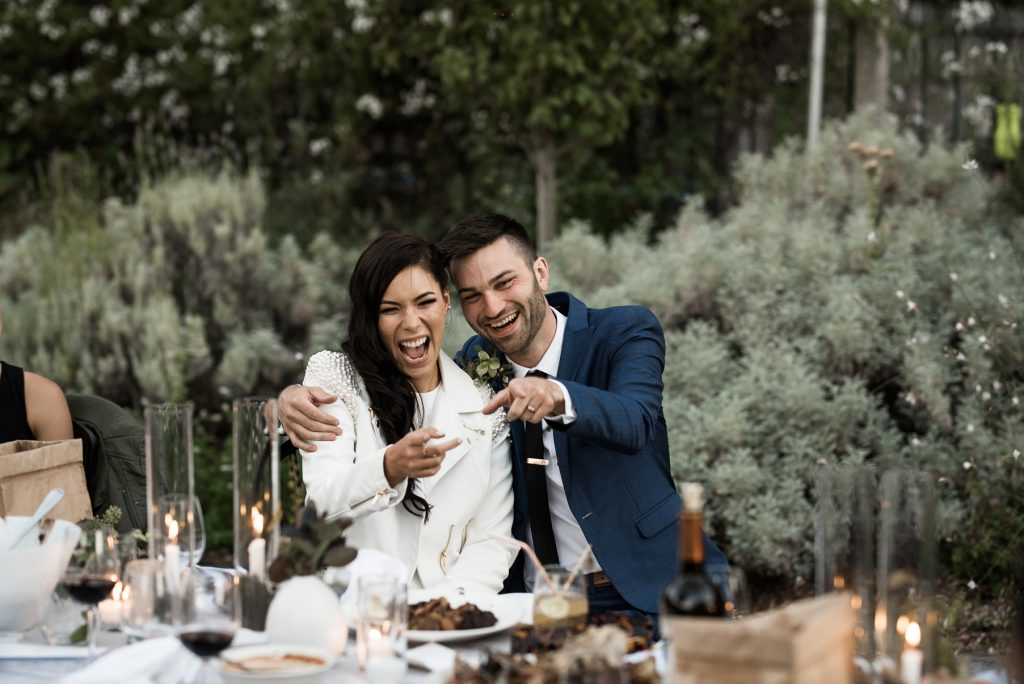 bride and groom laughing with loved ones during their wedding dinner