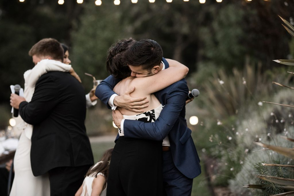 groom hugging his sister during their wedding speeches