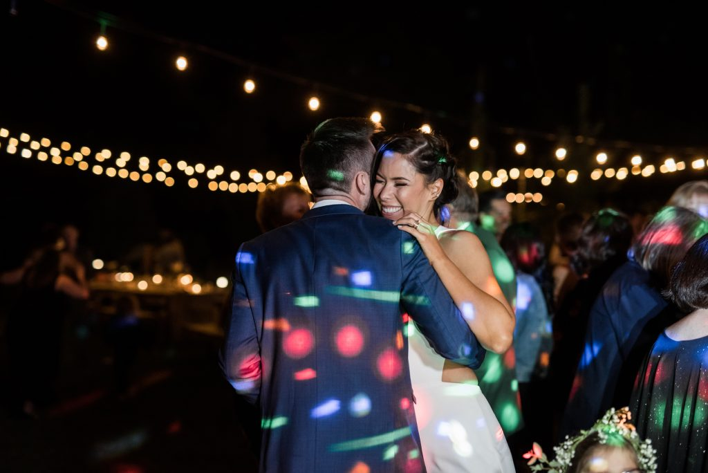 bride and groom dancing in colorful dj lights