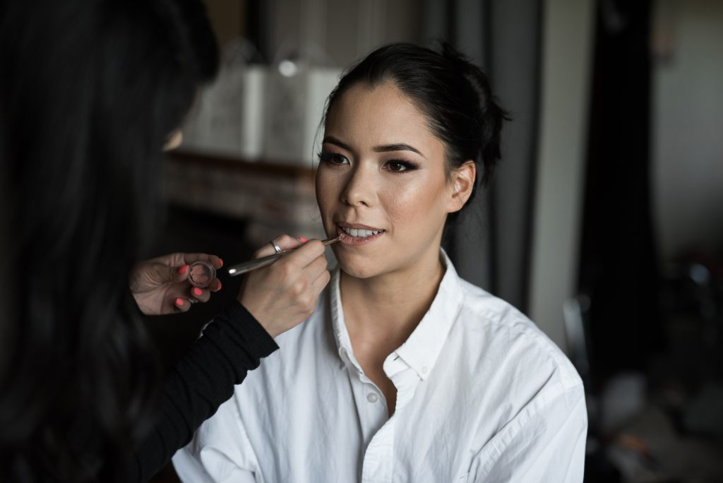 bride applying nude lipstick for wedding