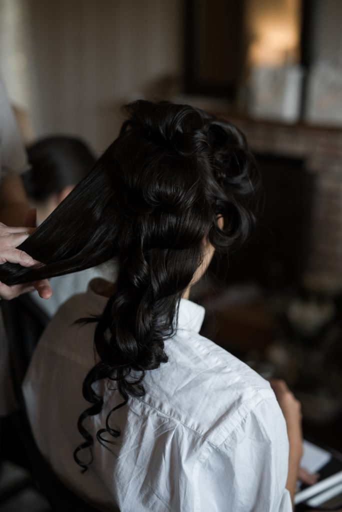 bride getting her hair styled with classic side swept curls