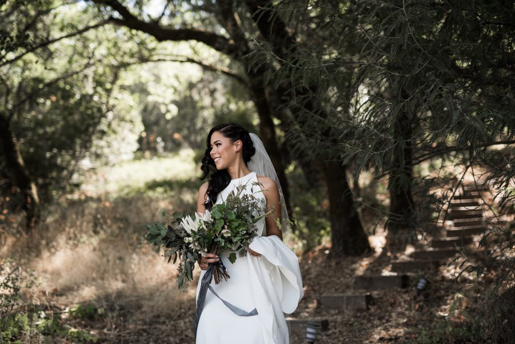 a bride looking to her fiance before the first look