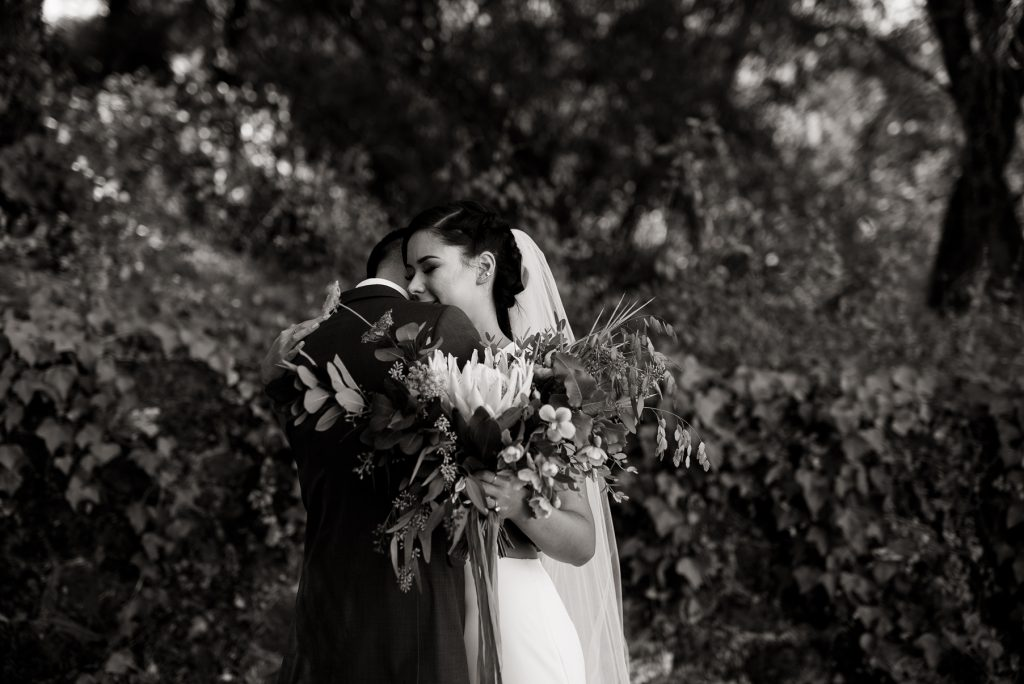 intimate hug between bride and groom in black and white