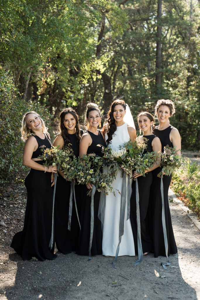 bridesmaids wearing black jumpsuits and greenery bouquets