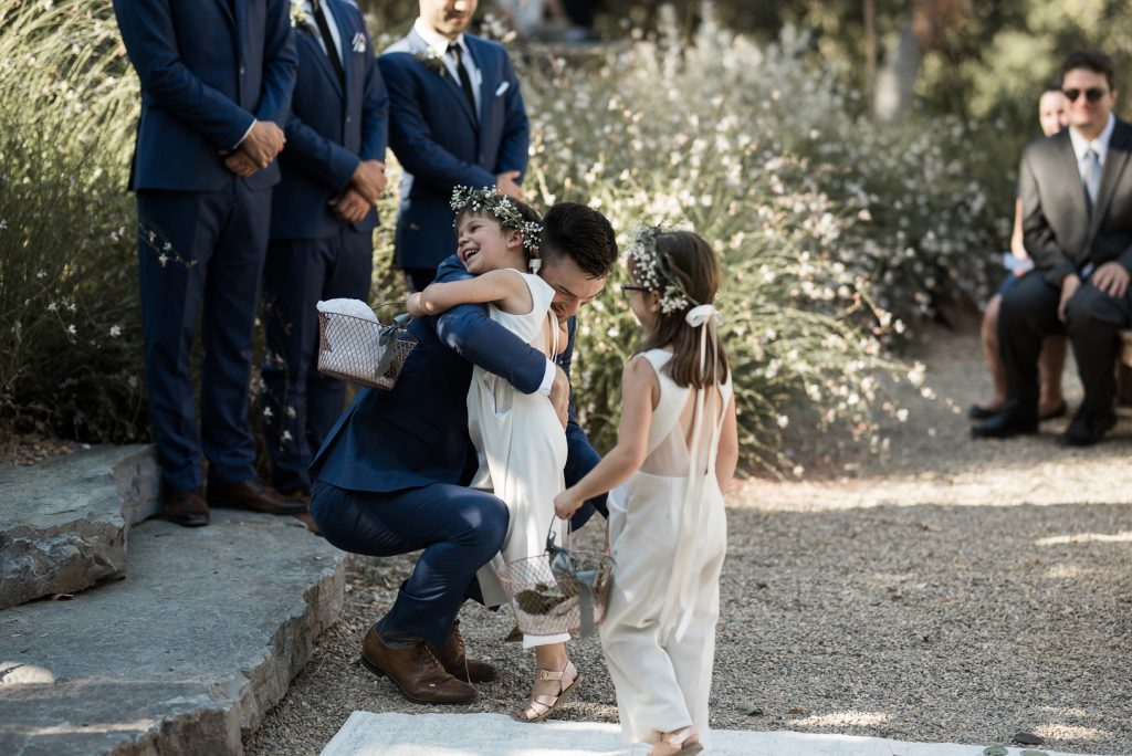 flower girl hugging the groom at yokayo ranch