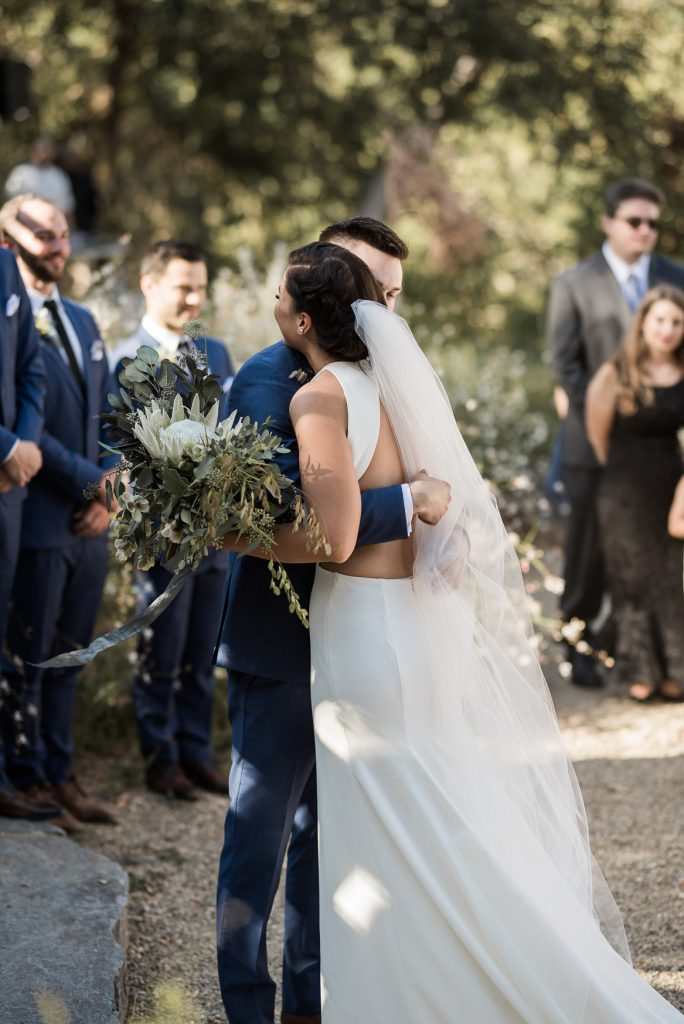 bride and groom hugging at the end of the aisle