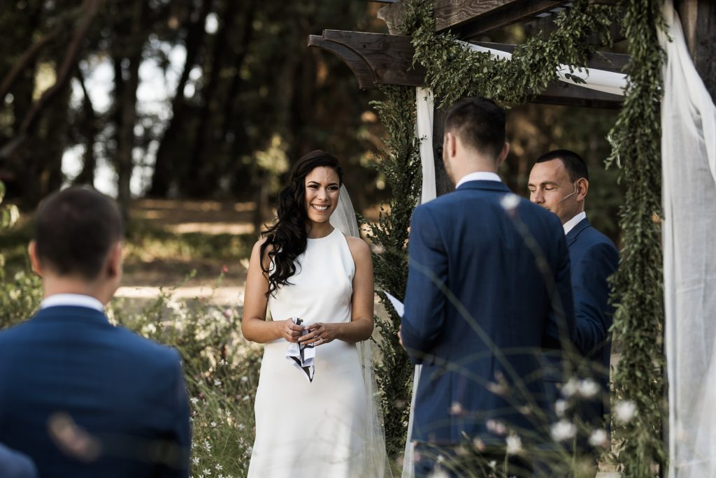 bride smiling at the grooms wedding speech