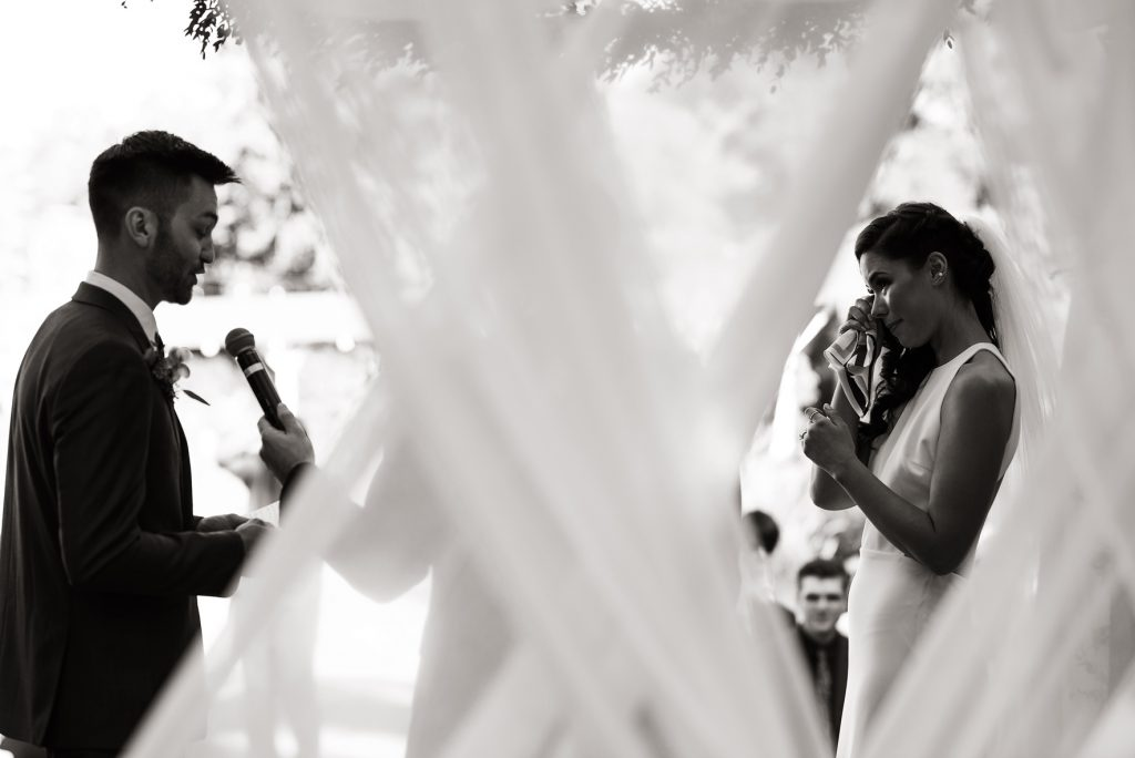bride wiping happy tears during wedding vows