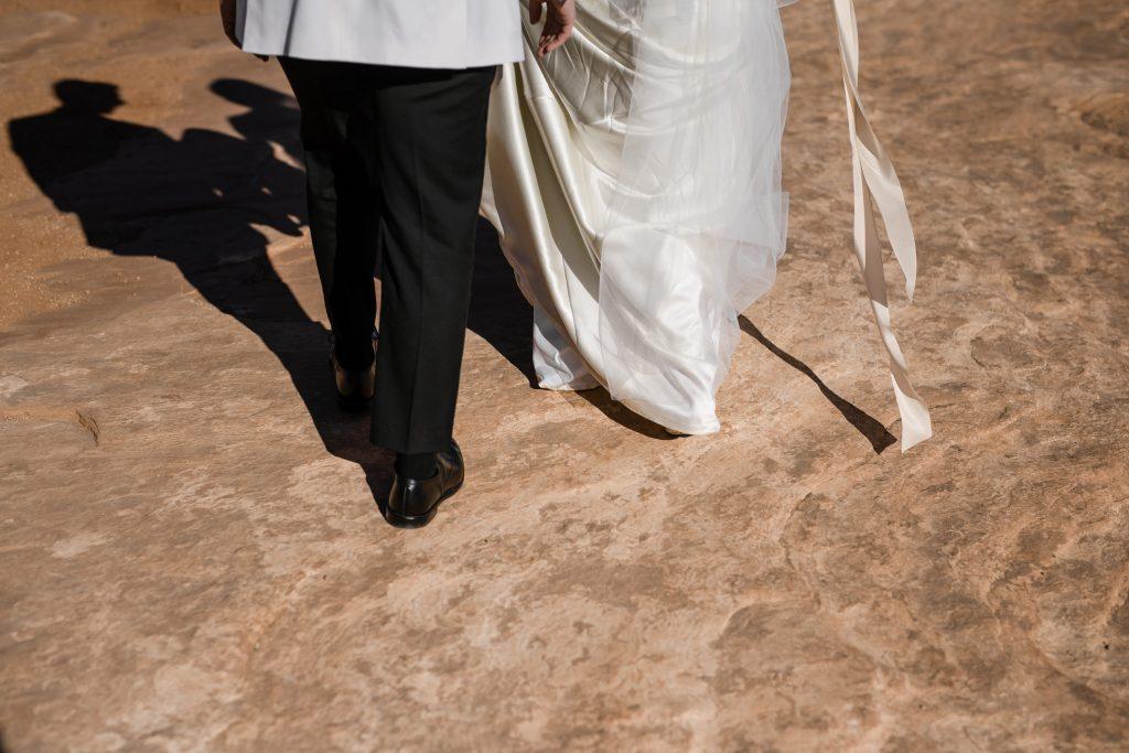 Bride and groom walking on Utah red rock