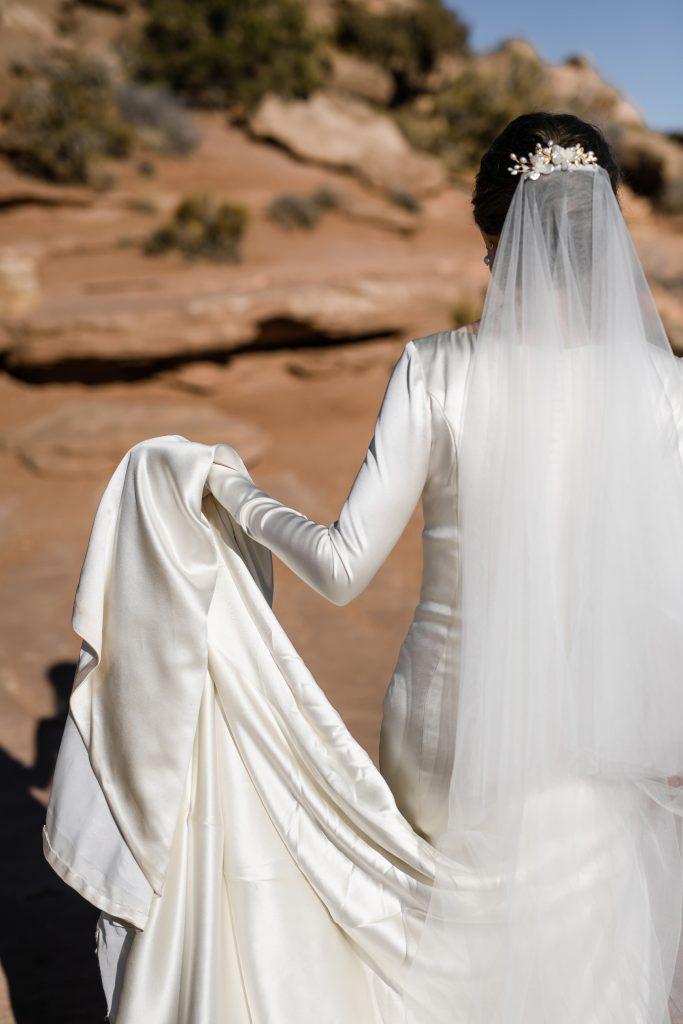 Bride holding dress from desert rock