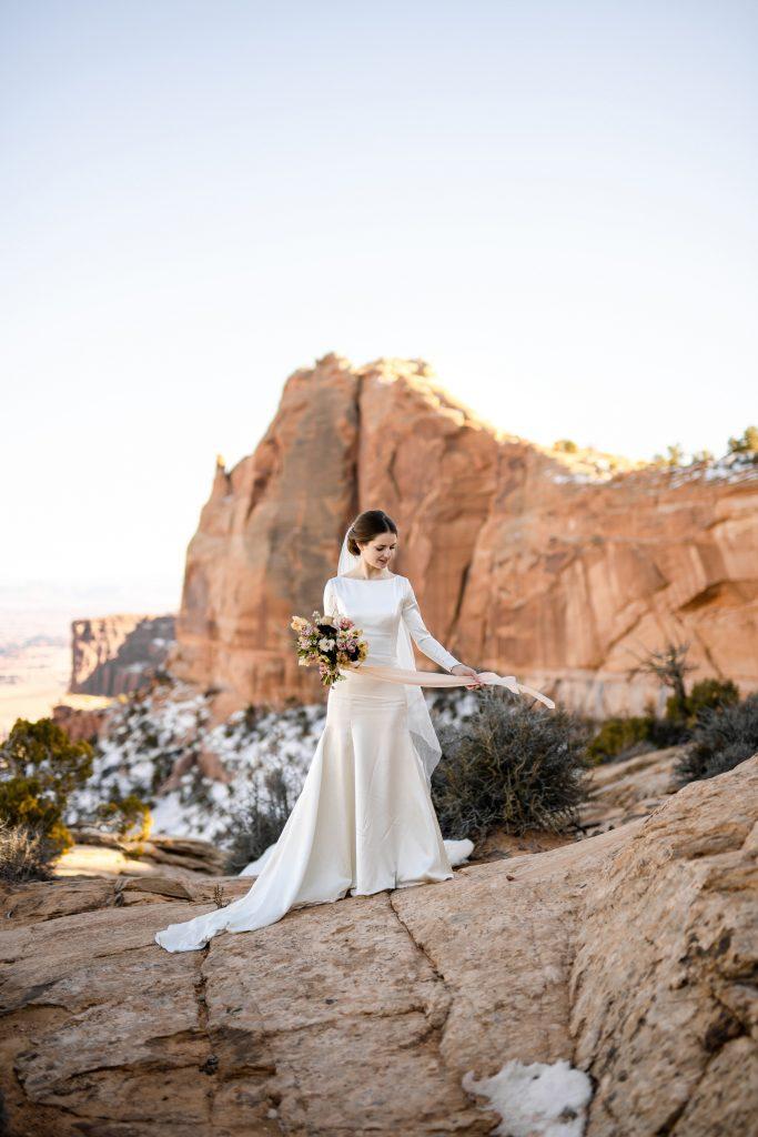 Bride standing near mesa arch