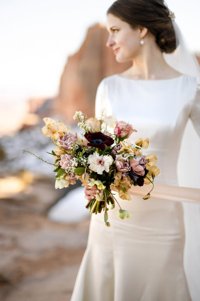 Bride holding colorful wedding bouquet in desert