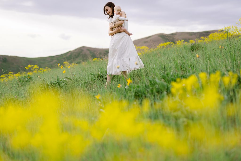 Mom and daughter walking through flowery field