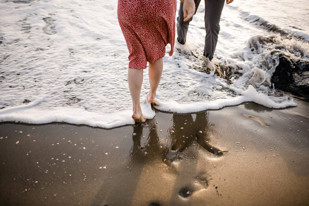 Couple walking barefoot under Golden Gate Bridge